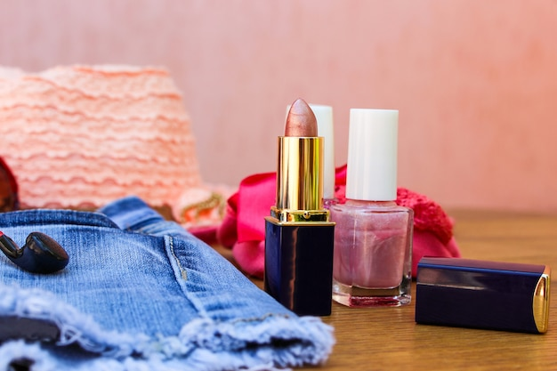 Cosmetics and women's accessories: lip gloss, nail polish, hat, denim shorts and headphones on table