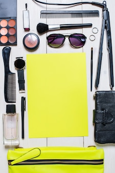 Cosmetics and womens accessories fell out of the green handbag on white background