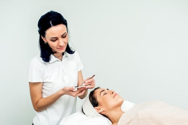 まつげエクステの手順中の美容師と患者。
