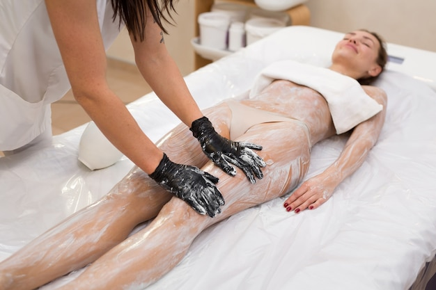 美容師は、ラッピング手順の前に、美容クリニックで若い女の子の体に保湿マスクを適用します。ボディケア。スパトリートメント。