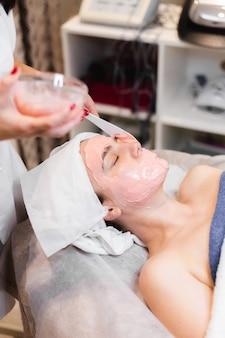 Il cosmetologo applica la maschera di alginato con la spatola sul viso della donna.