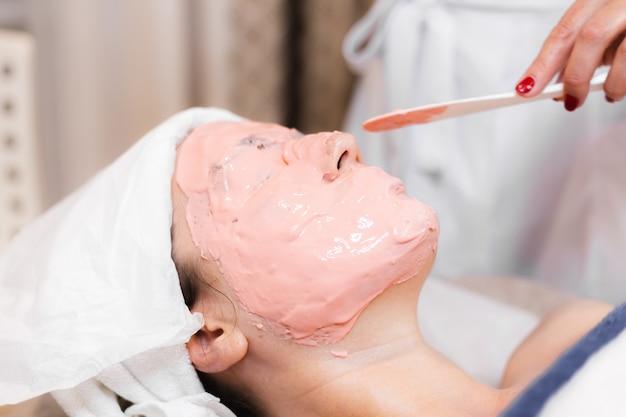 美容師は、女性の顔にヘラでアルギン酸塩マスクを適用します。