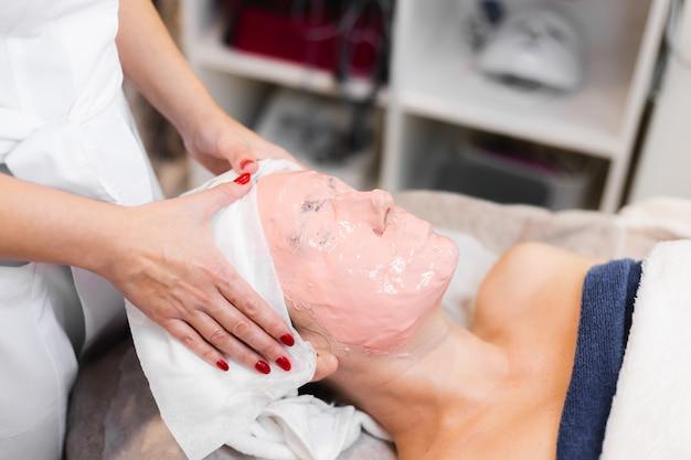 Косметолог наносит на лицо женщины альгинатную маску шпателем.