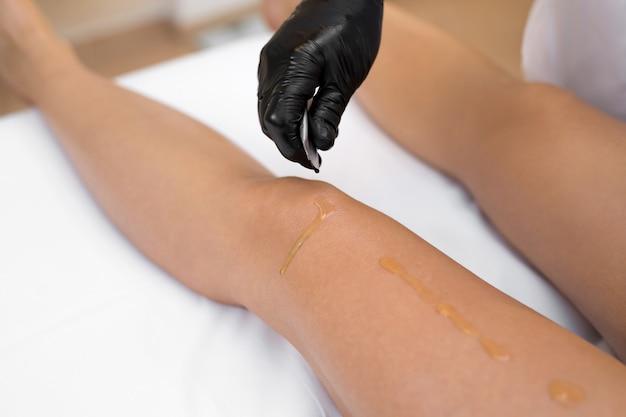 Косметолог перед обертыванием наносит масляный скраб на тело стройной молодой девушки. уход за кожей тела. гидромассаж.