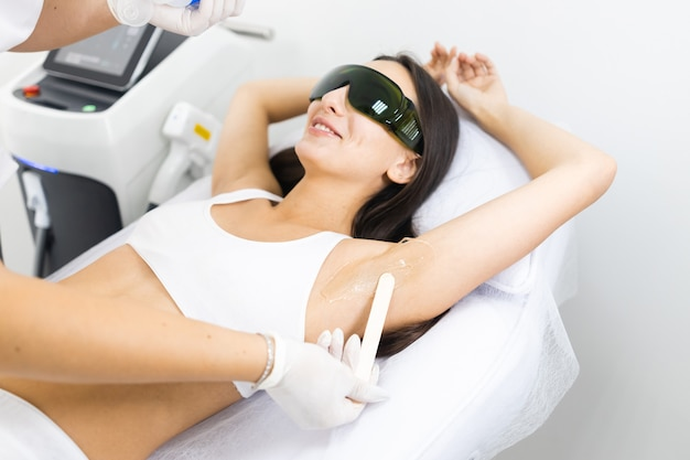 Cosmetologist applies gel for laser hair removal to woman armpit