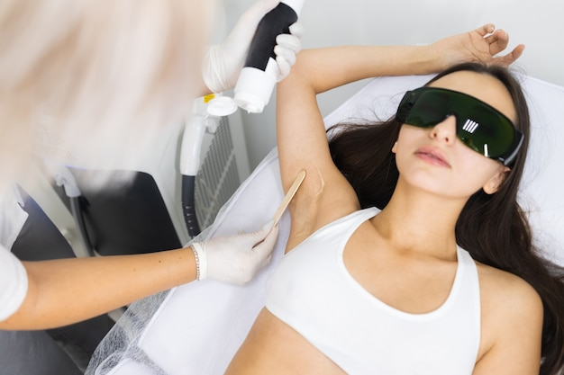 Cosmetologist applies laser hair removal gel to female client armpit