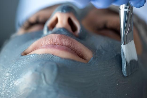 미용사는 스파 살롱에서 얼굴 젊은 예쁜 여자에 마스크를 적용