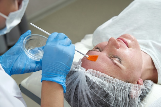 Cosmetologist applies oil to the client face in the beauty salon