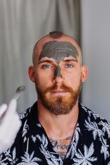 美容クリニックで若いハンサムな男の顔にブラシで粘土マスクを適用する美容師