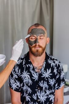 미용사는 뷰티 클리닉에서 젊은 잘 생긴 남자의 얼굴에 브러시로 클레이 마스크를 적용합니다.