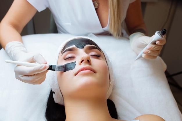 Косметолог, применяя черную маску на лице красивой женщины в черных перчатках, великолепная женщина в спа-салоне