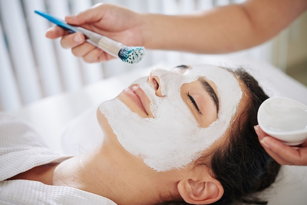 Cosmetologist applying clay mask