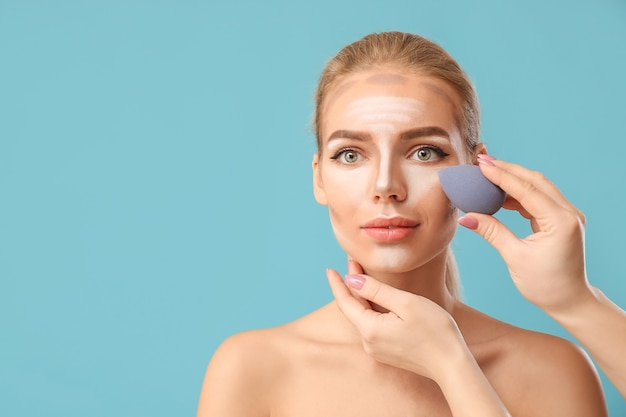 Косметолог, применяя контурный макияж на женском лице против цвета