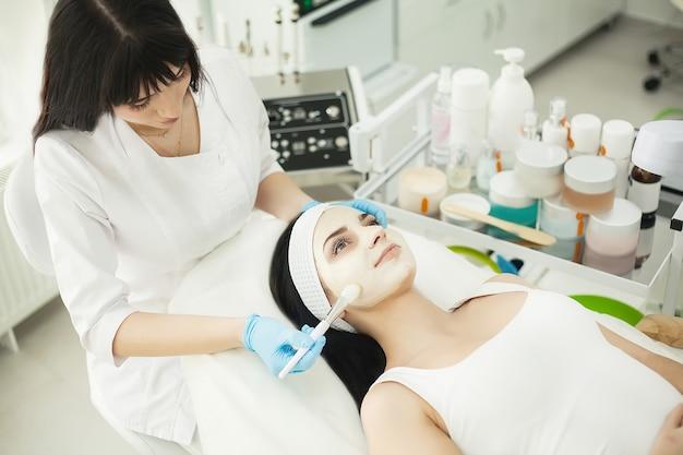 Косметолог наносит крем для лица клиенту в косметологическом кабинете