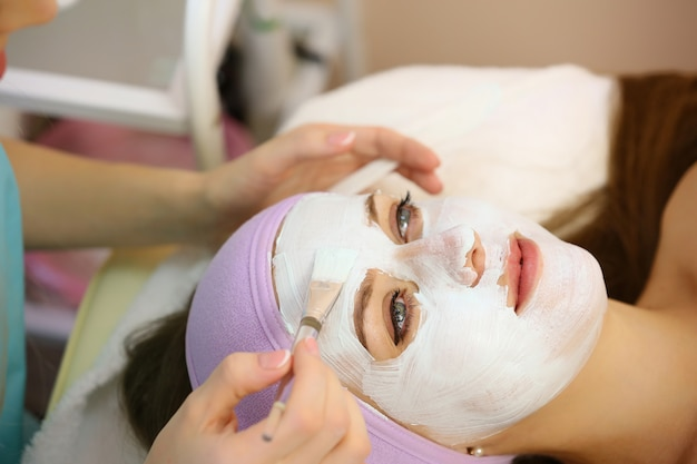 Cosmetologist applying facial mask in beauty salon.