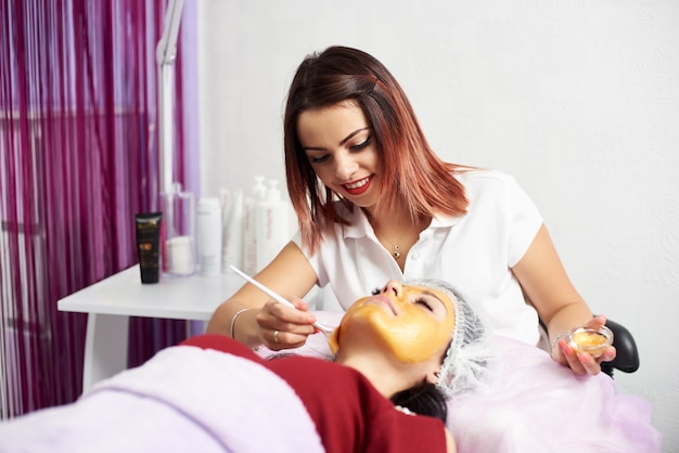 Cosmetologist applying gold mask on patient