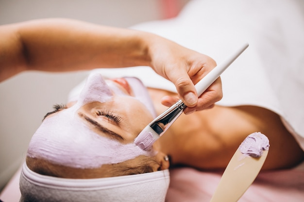 Cosmetologist applying mask on a face of client in a beauty salon