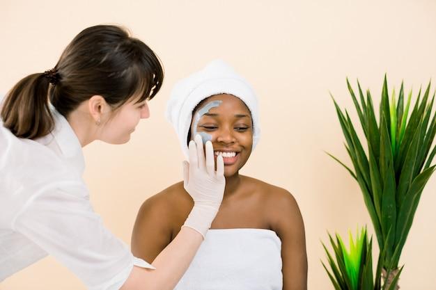 美容師がスパサロンでアフリカ系アメリカ人女性の顔にマスクを適用します。美容とスキンケアのコンセプト