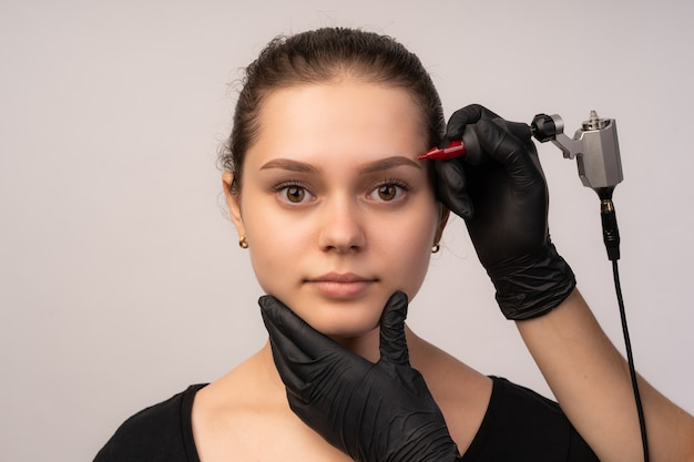 Косметолог, применяя перманентный макияж на брови.