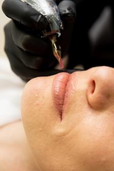 Косметолог, наносящий перманентный макияж на губы в салоне красоты