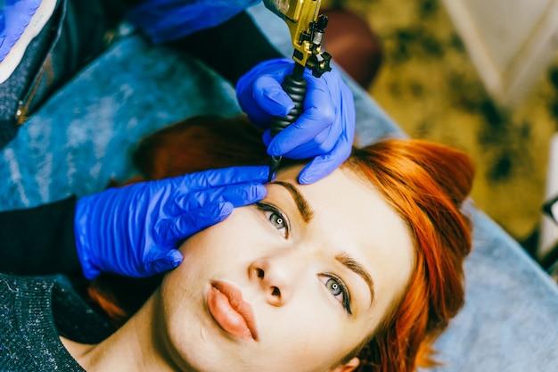 眉毛にアートメイクをする美容師。アートメイク。セレクティブフォーカスと浅いクローズアップ。