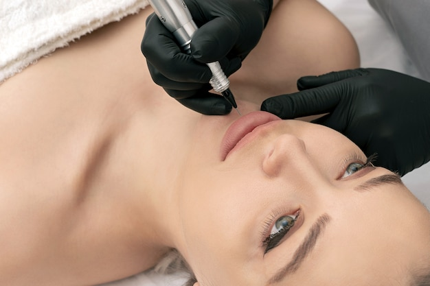 Косметолог наносит татуаж на губы