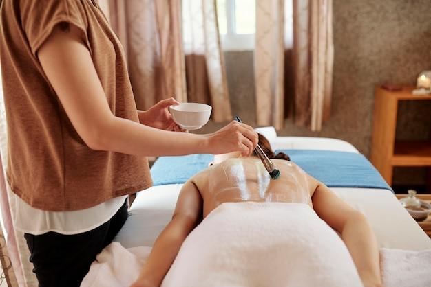 Cosmetologist applying skin treatment