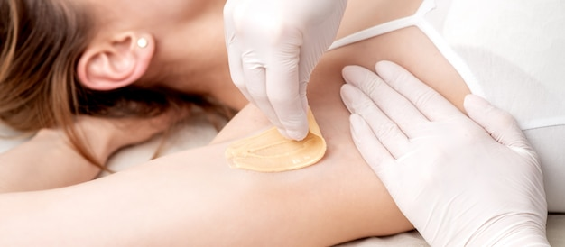 Cosmetologist applying wax paste on armpit