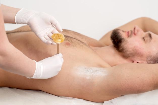 Косметолог наносит восковую пасту на подмышку