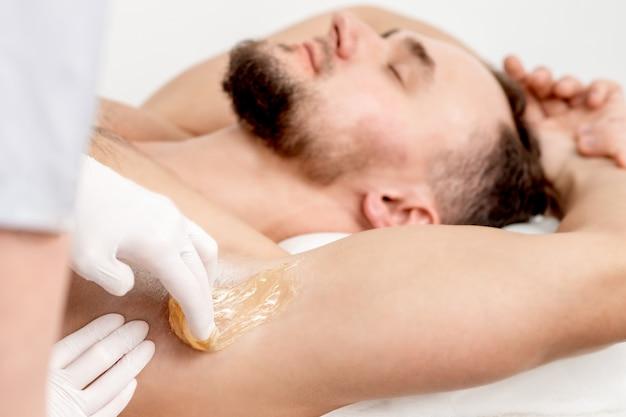 Косметолог наносит восковую пасту на мужскую подмышку