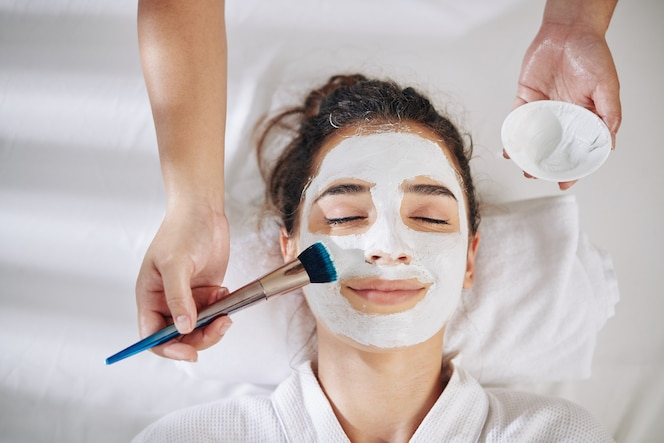 Cosmetologist applying white clay mask