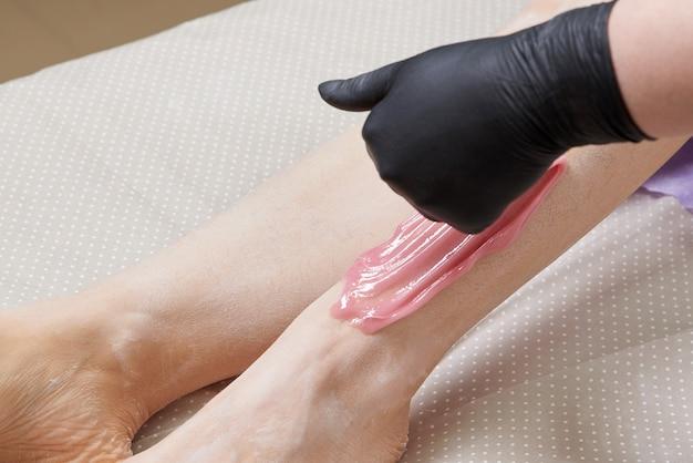 スパセンターの美容院の美容コンセプトで女性の足にワックスをかける美容師の美容師