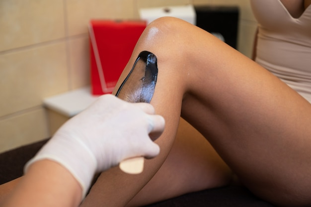 Cosmetologist in beauty clinic performs a epilation procedure for removing hair from the female leg ...