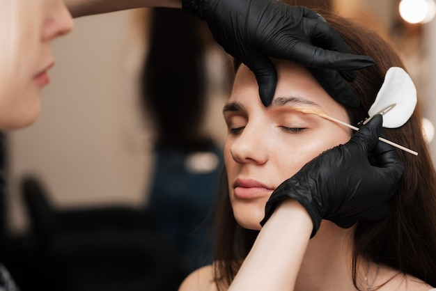 The cosmetologist-brovist corrects and gives shape, plucks out excess hairs in the eyebrows with wax in the beauty salon. professional facial care