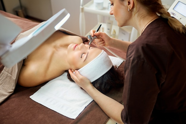 Cosmetologist dermatologist makes a woman a procedure bio oxidation therapy.