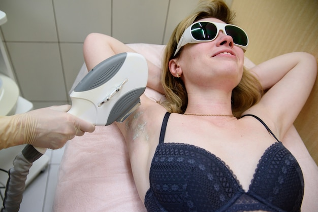 The cosmetologist does the laser hair removal procedure in the armpit zone