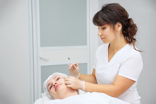 Cosmetologist does medical procedure with collagen filler
