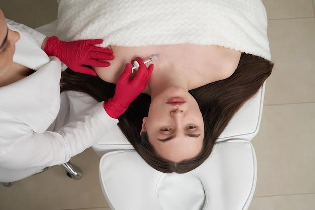 Косметолог делает прп терапию на шее красивой женщины в салоне красоты. косметология