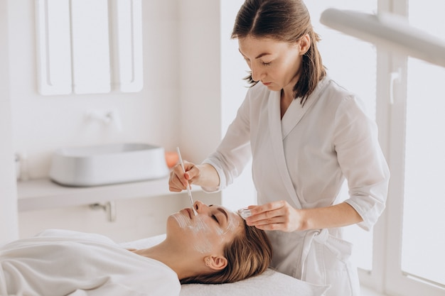 Cosmetologist doing face treatment and applying face mask