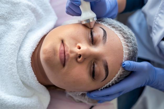 Косметолог делает процедуру фонофореза для молодой женщины, лежащей на диване