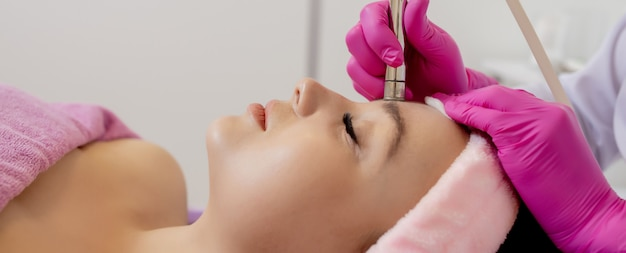 Cosmetologist doing the procedure microdermabrasion of the facial skin