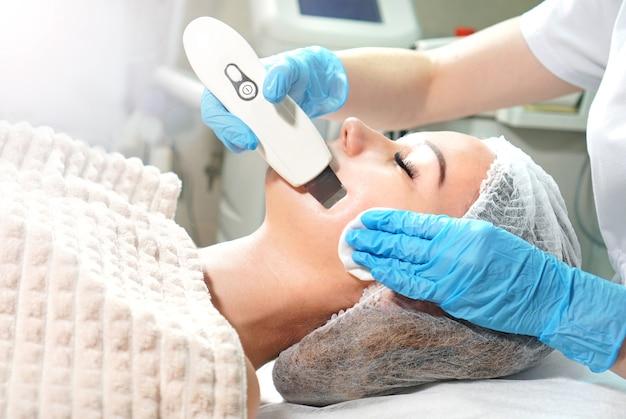 Косметолог делает для молодой женщины ультразвуковой пилинг лица.