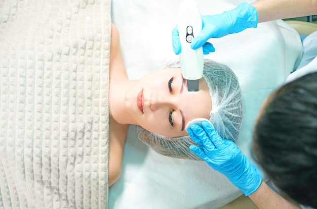 Cosmetologist doing ultrasound face peeling for the young woman, view above