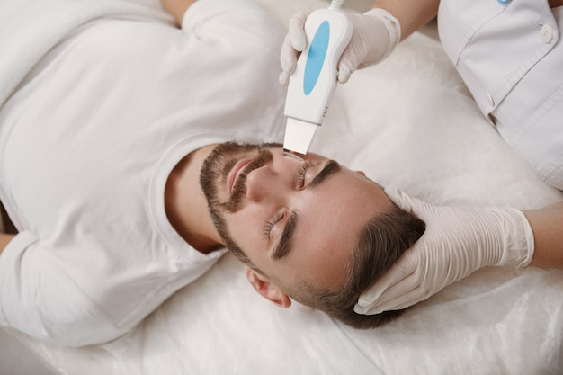 Cosmetologist doing ultrasound skin pores cleanse for her male client
