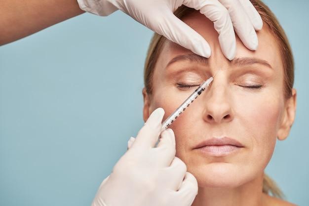成熟した女性のために眉間のしわに注射を与える美容師