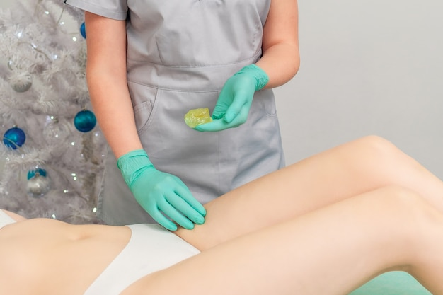 Cosmetologist in gloves applying paste for sugaring depilation