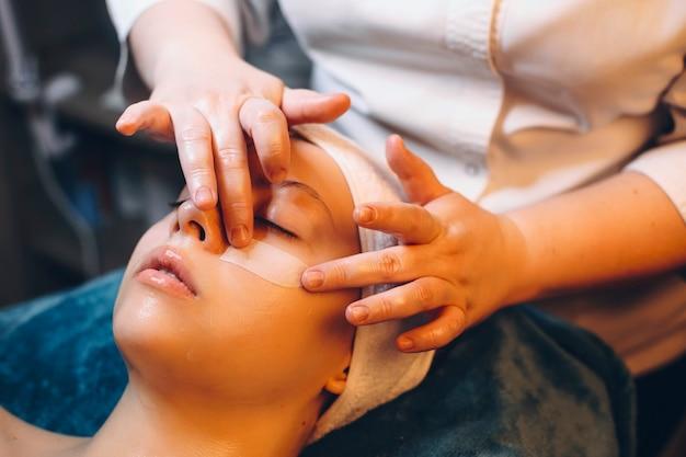 Рука косметолога наносит антивозрастную маску на женское лицо на оздоровительном курорте.