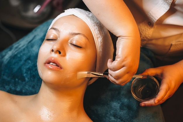 Cosmetologist hand holding a cup with anti age mask with hyaluronic acid and a brush applying mask on a female face in a wellness resort.