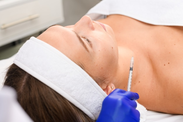 Рука косметолога в синей медицинской перчатке со шприцем для инъекций по уходу за кожей