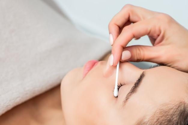 綿棒で女性の目を拭く美容師の手。